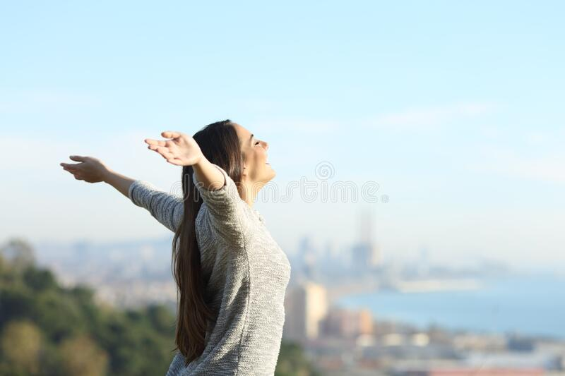 Happy woman stretching arms breathing fresh air outdoors royalty free stock photography