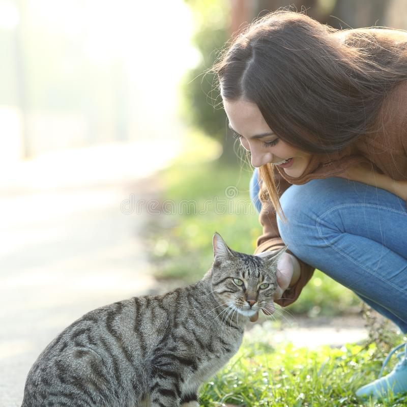 Happy woman stroking a cat in a park stock photography