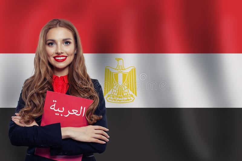 Happy woman student with red book on the Egypt flag background. Egypt, travel and learn arabic language concept. Book with inscription Arabic on Arabic stock photography