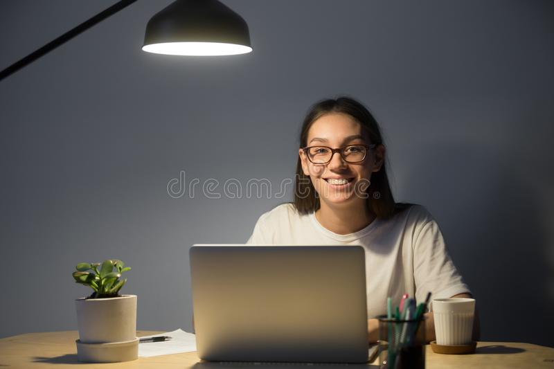 Happy freelancer smiling to camera posing at office desk royalty free stock photo