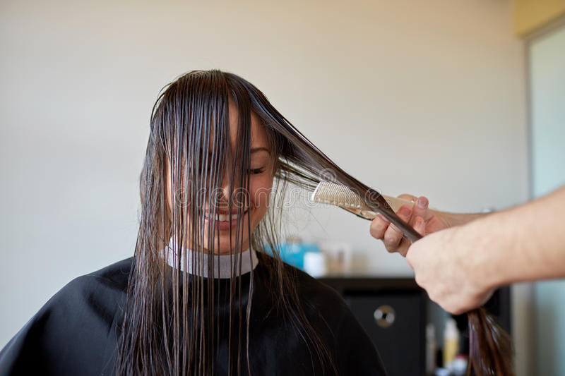 Happy woman with stylist cutting hair at salon. Beauty, hairstyle and people concept - happy young women and hairdresser hands with scissors and comb cutting royalty free stock images