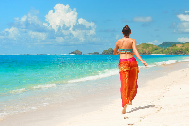 Happy woman in summer loose trousers running on tropical beach stock photos