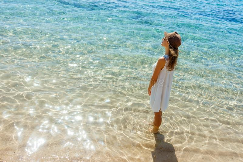 Happy woman in summer white dress on beach. girl relaxing and enjoying peace on vacation stock photo