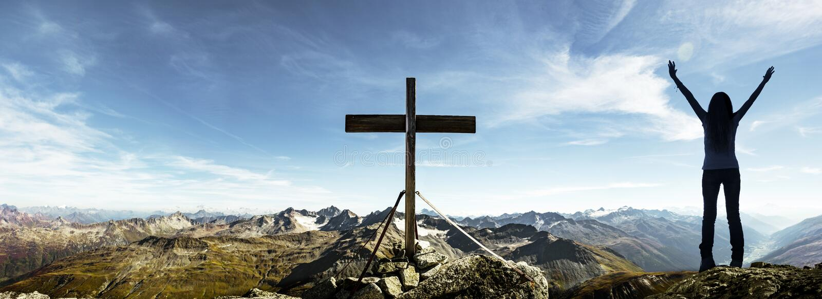 Happy woman at summit cross stock images