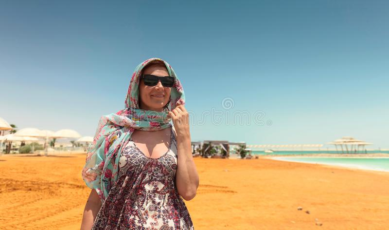 Happy woman in sunglasses on a beach of dead sea royalty free stock photo
