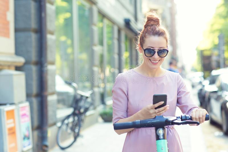 Happy woman in sunglasses using smartphone and renting modern electric scooter with an application stock photography