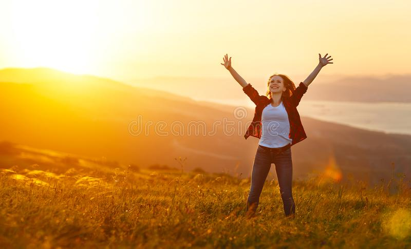 Happy woman on sunset in nature iwith open hands royalty free stock photo