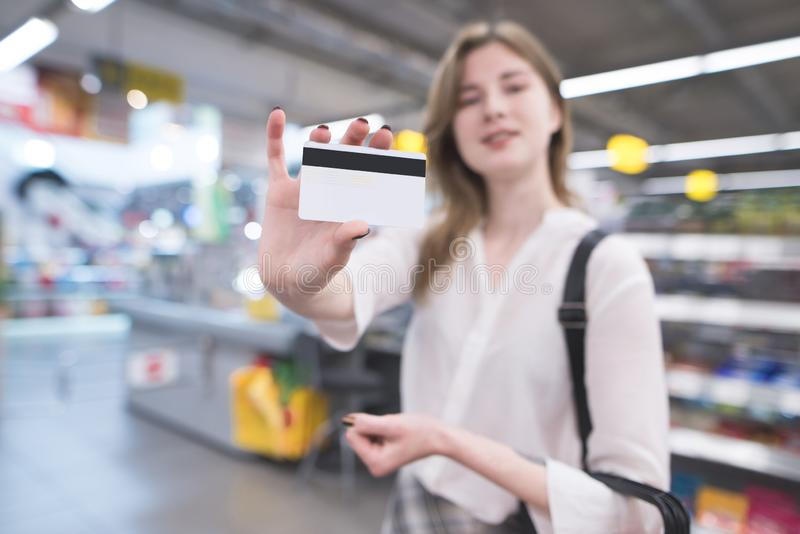 Happy woman is in the supermarket and shows a credit card. Credit card is in the hands of the buyer in the store stock photography