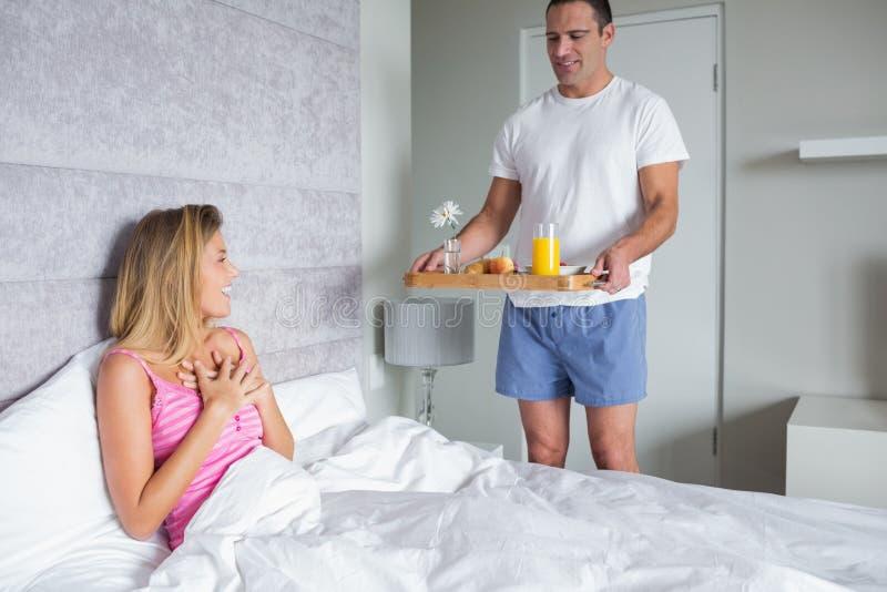 Happy woman surprised by partner bringing breakfast in bed. Happy women surprised by partner bringing breakfast in bed at home in bedroom stock photos