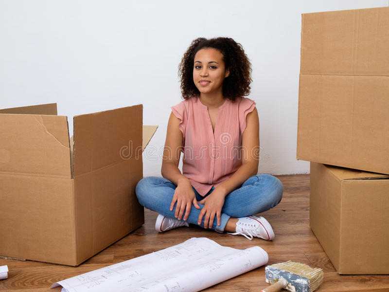 Happy woman surrounded by large boxes stock photo