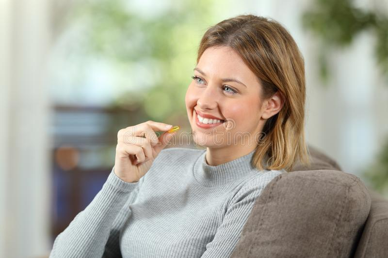 Happy woman takes a vitamin pill on a couch. Happy woman takes a vitamin pill sitting on a couch in the living room at home stock image