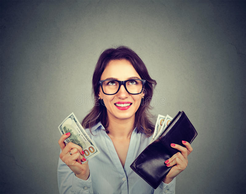 Happy woman taking money out of wallet stock photo
