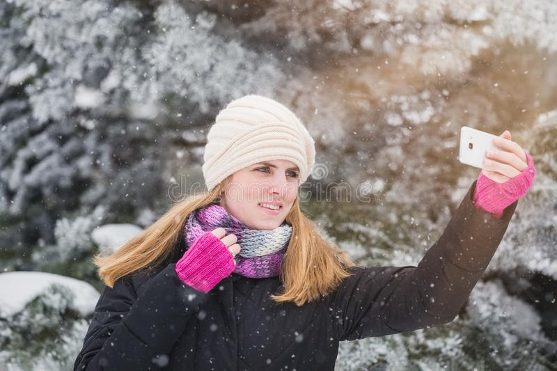 Cheerful woman taking self portrait by using her smart phone. stock photo
