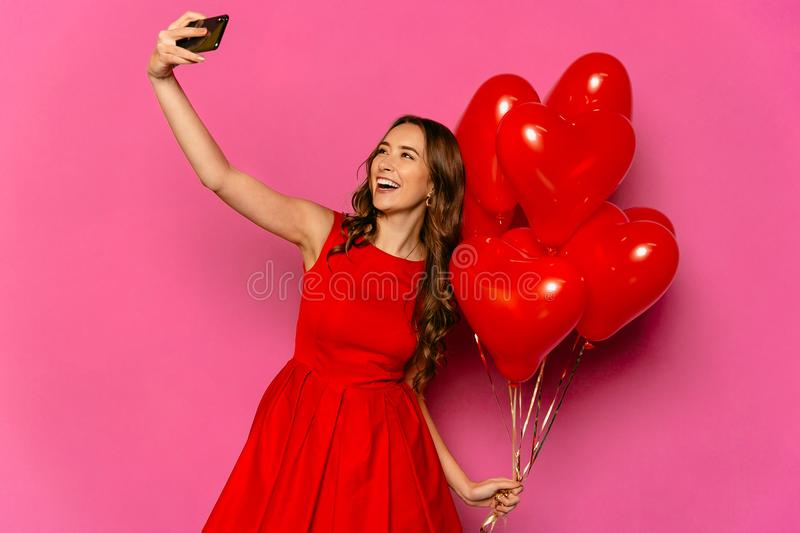 Happy woman taking selfie on smartphone with red balloons on Valentine`s day. Young charming woman taking selfie on smartphone with heart shaped air balloons stock images