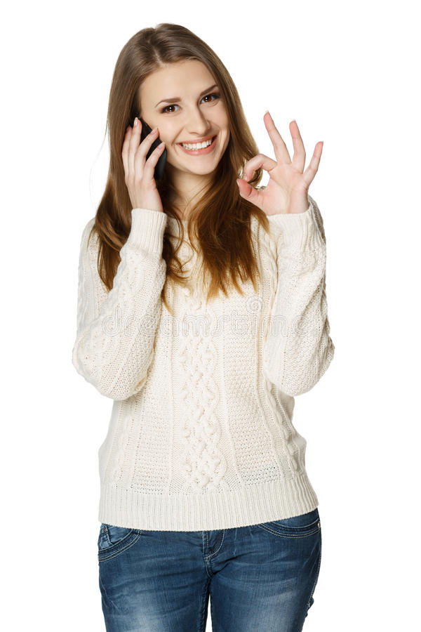 Happy woman talking on cell phone and showing OK royalty free stock photo