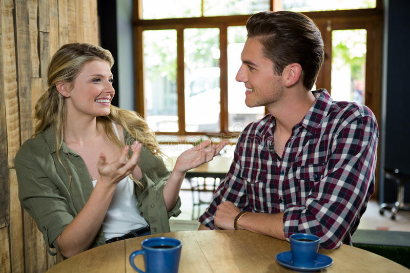 Happy woman talking with man at table in coffee shop stock images