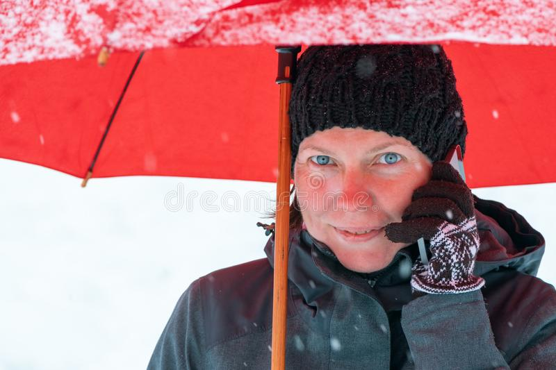 Happy woman talking on mobile phone under umbrella in snow stock image