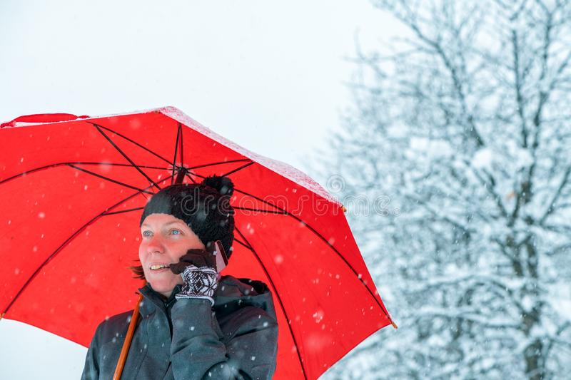 Happy woman talking on mobile phone under umbrella in snow royalty free stock photo