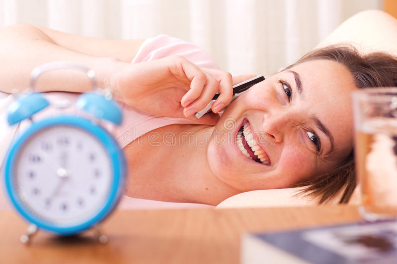 Happy woman talking on phone. Attractive happy woman talking on the phone in bed stock images