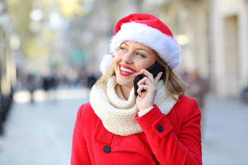 Happy woman talking on phone on christmas in the street. Happy woman in red wearing a santa claus hat talking on phone looking at side on christmas in the street royalty free stock image