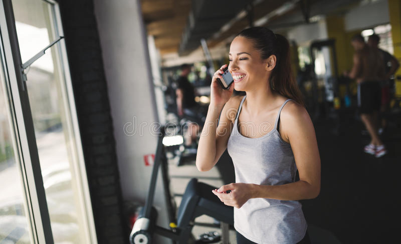 Happy woman talking on phone in gym royalty free stock photography