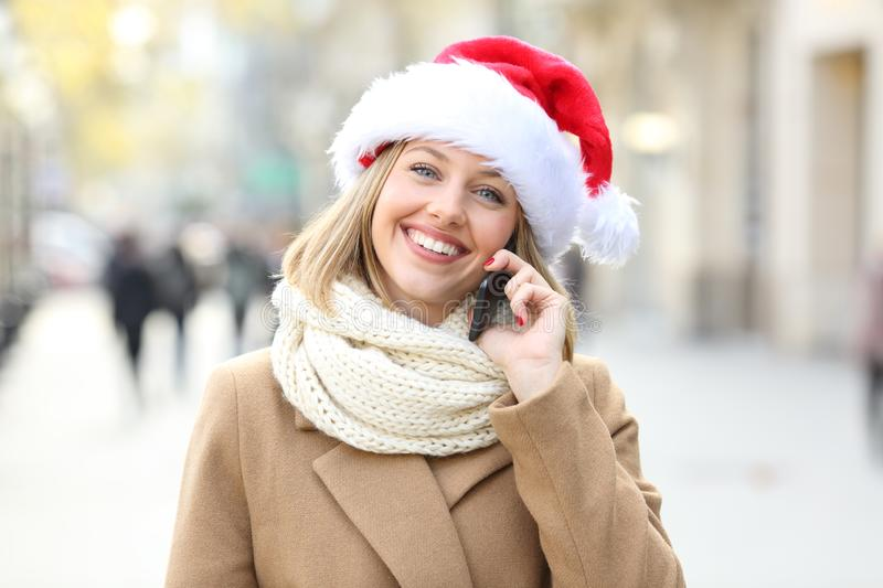 Happy woman talking on phone looking at you in christmas. In the street royalty free stock photos