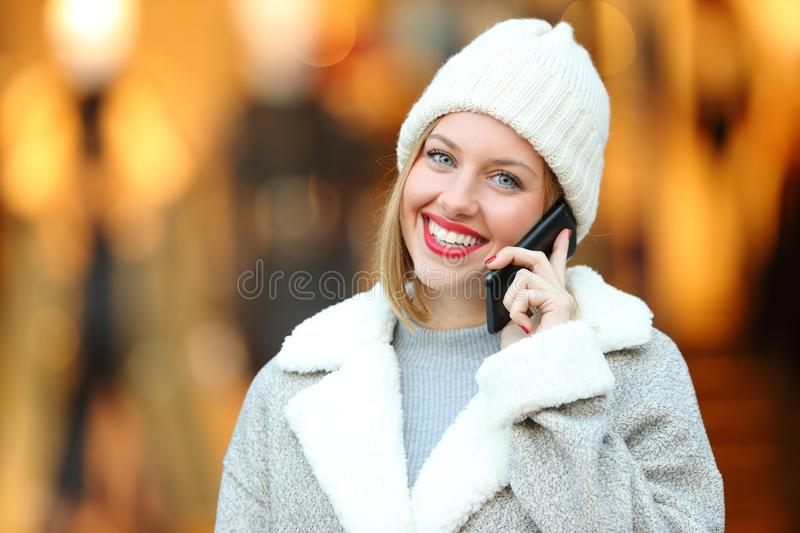 Happy woman talking on phone looking at you in winter. Happy woman talking on smart phone looking at you in winter in the street stock photo