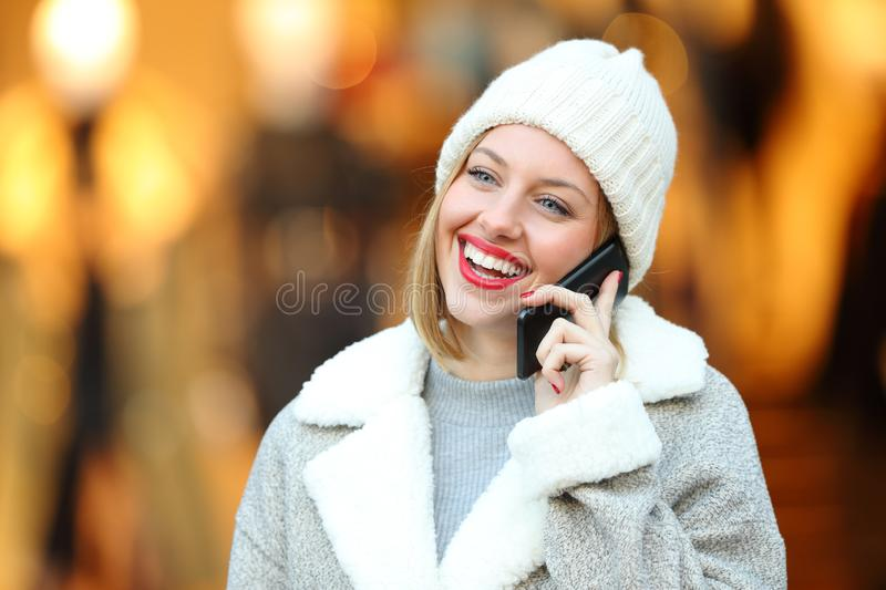 Happy woman talking on phone in winter in a mall. Happy woman talking on phone in winter standing in a mall stock photos