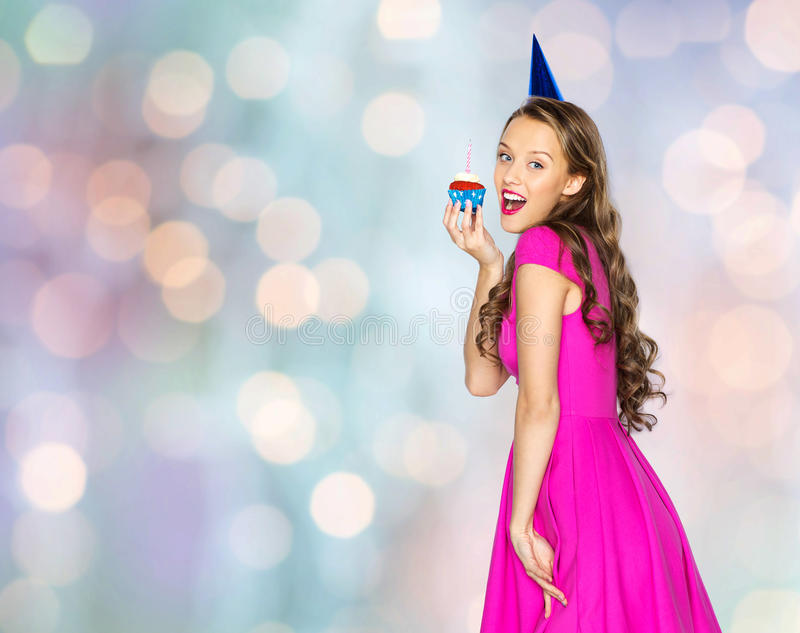 Happy woman or teen girl with birthday cupcake. People, holidays and celebration concept - happy young woman or teen girl in pink dress and party cap with stock photography
