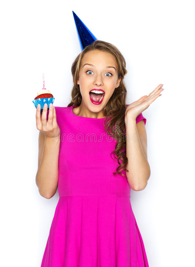 Happy woman or teen girl with birthday cupcake. People, holidays, emotion, expression and celebration concept - happy young woman or teen girl in pink dress and stock photos