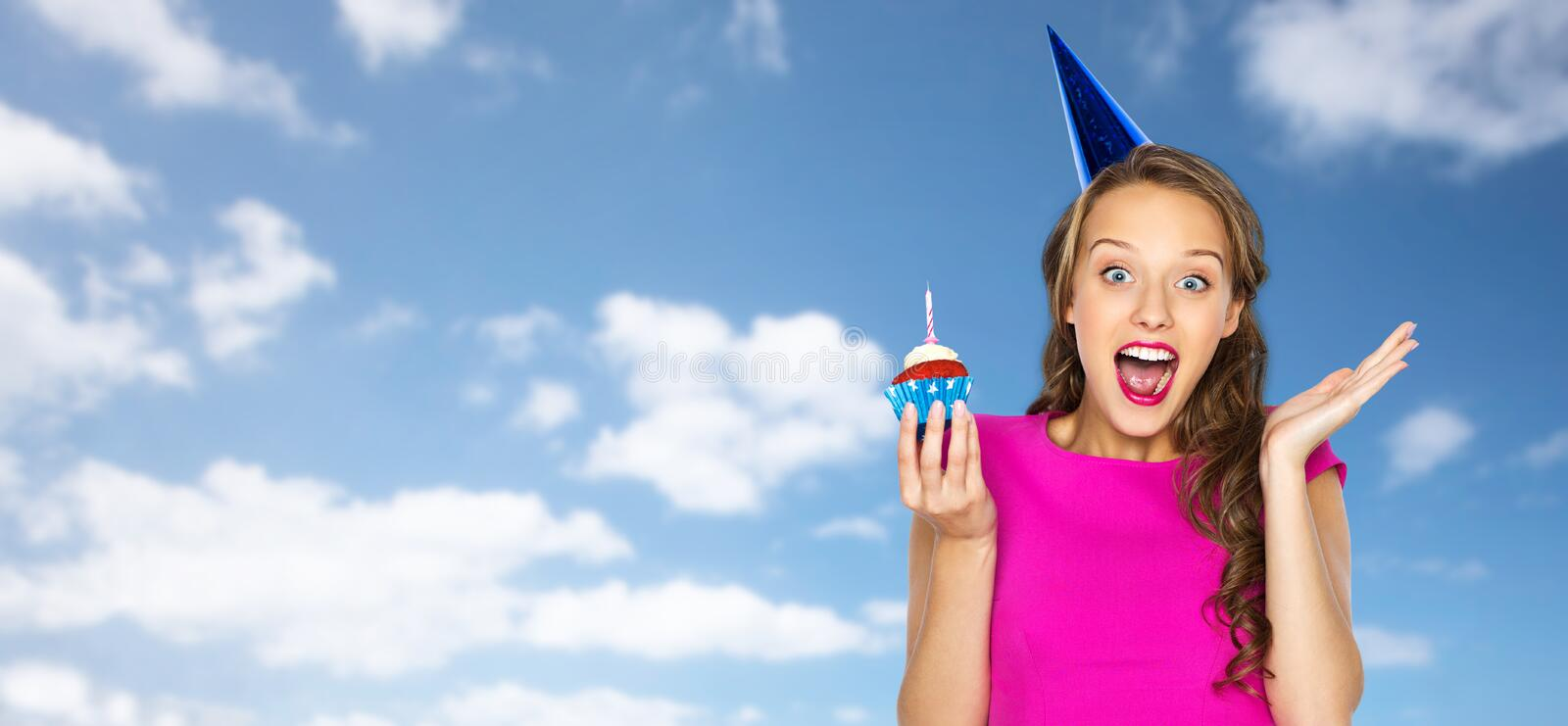Happy woman or teen girl with birthday cupcake. People, holidays, emotion, expression and celebration concept - happy young woman or teen girl in pink dress and stock photography