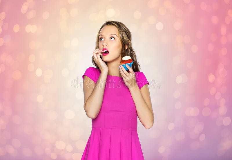 Happy woman or teen girl eating birthday cupcake. People, holidays, party, junk food and celebration concept - happy young woman or teen girl in dress eating stock photos