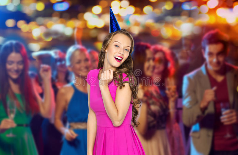 Happy woman or teen in party cap at night club. People, holidays, night life and celebration concept - happy young women or teen girl in pink dress and party cap stock image