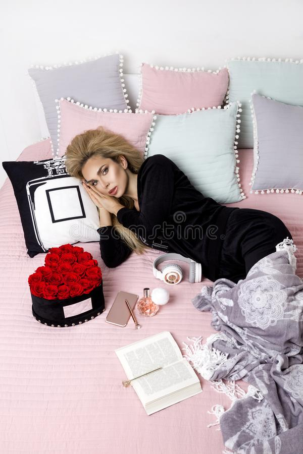 Happy woman or teenage girl with headphones listening to music from smartphone. Beautiful girl in pajama lying in bed royalty free stock photos