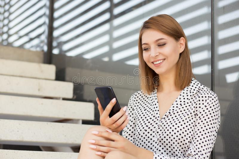 Happy woman texting on the phone, smiles and looks stock photo