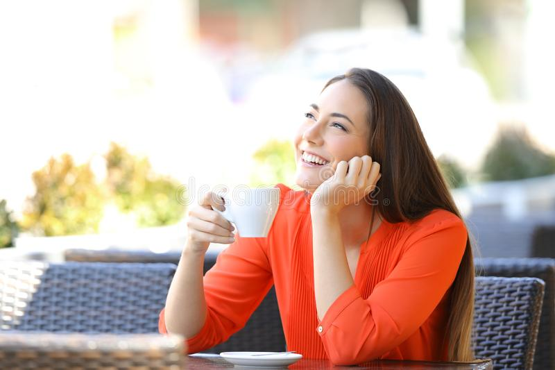 Happy woman thinking drinking coffee in a bar royalty free stock photos
