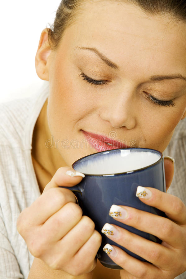 Happy woman thinking holding a cup of tea stock photo