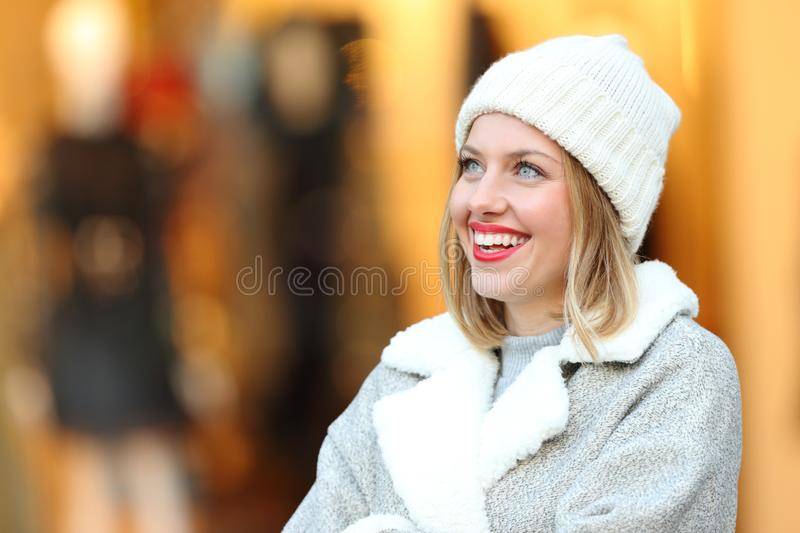 Happy woman thinking looking above in a mall. Happy woman thinking looking above standing in a mall in winter stock photography
