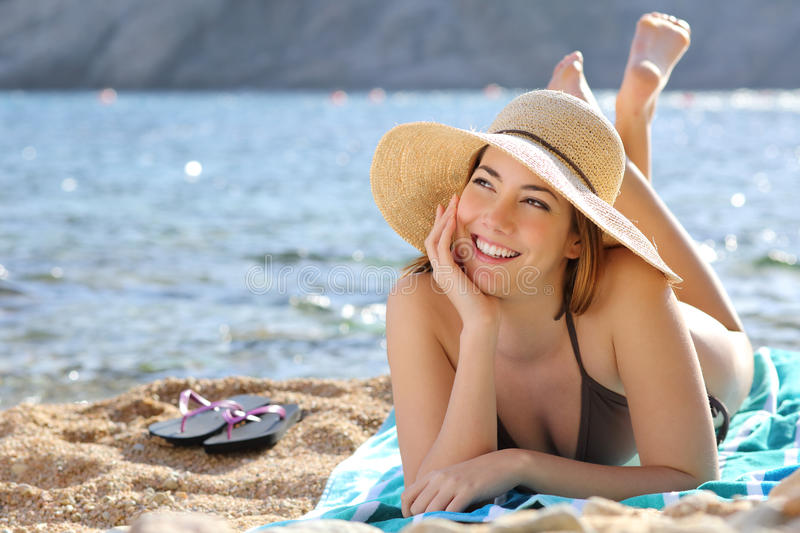 Happy woman thinking and looking at side lying on the beach stock photo