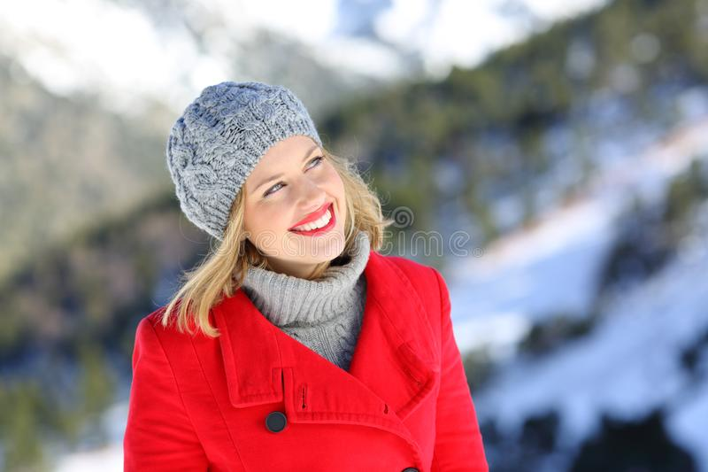 Happy woman thinking looking at side in winter holiday. Front view portrait of a happy woman in red thinking looking at side in winter holiday in the mountain stock images