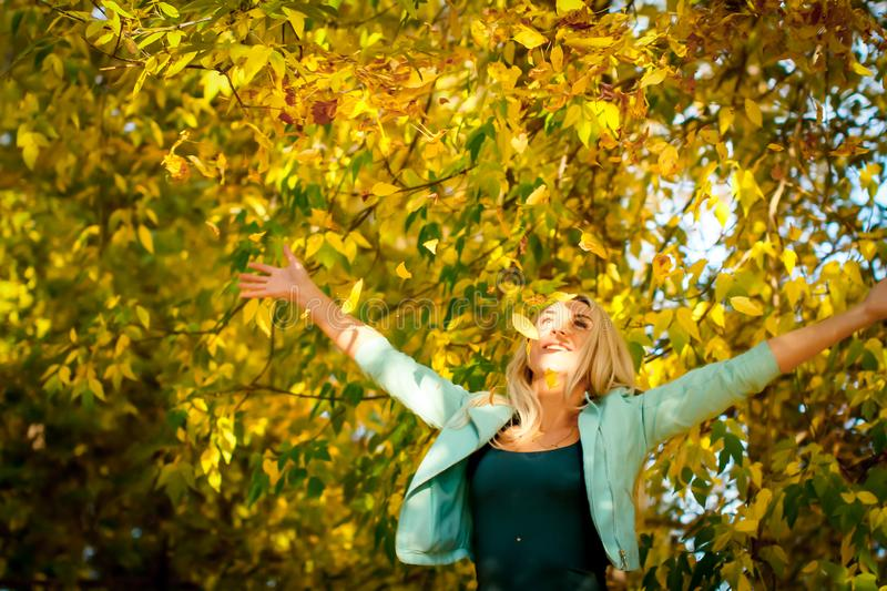 Happy woman throwing up leaves in autumn, smiling. A joyful and excited young woman happily throws yellow leaves in a royalty free stock photos