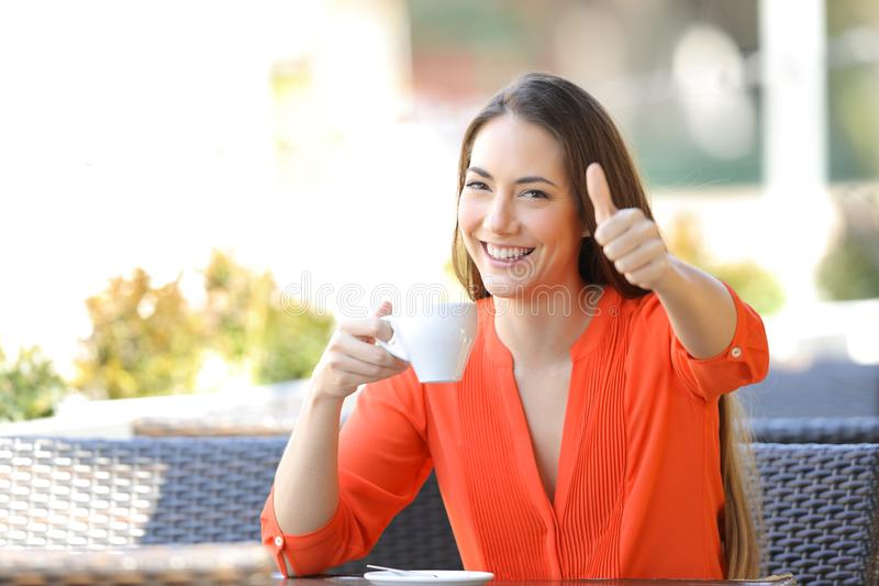 Happy woman with thumb up in a bar holding a coffee cup stock photo