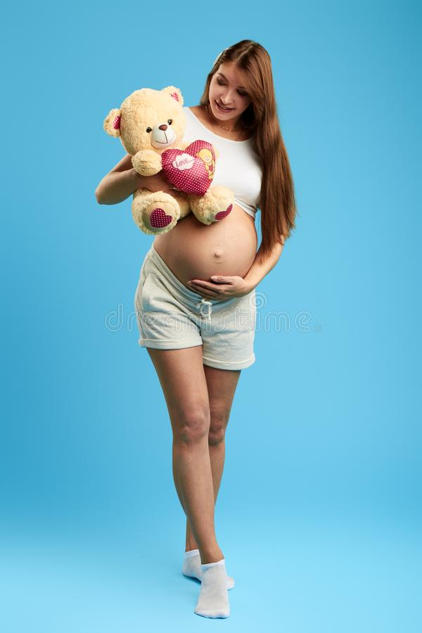 Happy woman touching her belly while carring the bear. Full length photo. fist present for baby. isolated blue background. studio shot stock photo