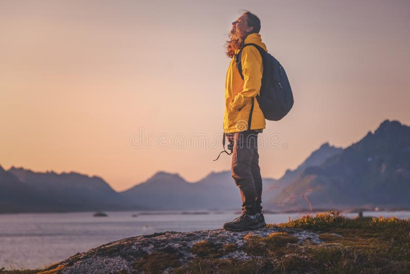 Happy woman tourist with relax and enjoy sunset on  Lofoten in Norway, mountains and sea background stock photography