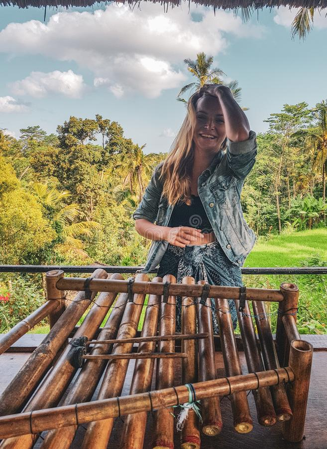 Happy woman tourist with traditional bamboo percussion intrument in Bali stock images