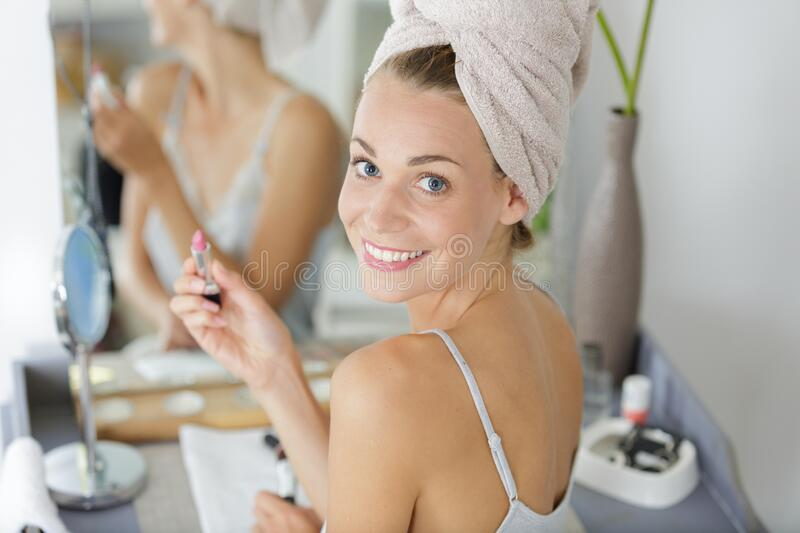 Happy woman with towel on head applying make-up stock images