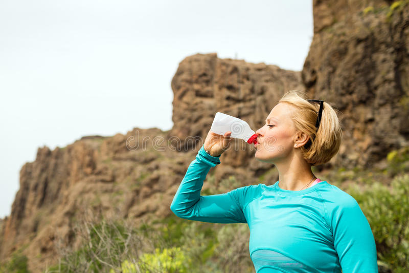Happy woman trail runner drinking water in mountains royalty free stock images
