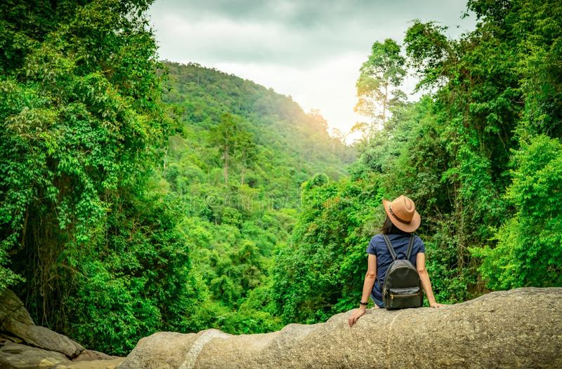 Happy woman travel alone in woods. Active woman with good mood sit on stone in green valley with dense tree in the forest. Happy stock image
