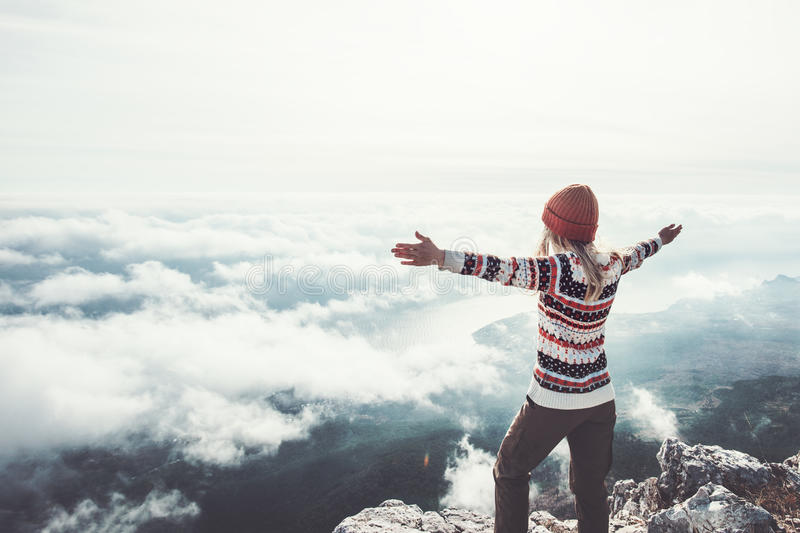 Happy woman traveler on mountain summit hands raised. Travel Lifestyle success concept adventure active vacations outdoor over clouds harmony with nature royalty free stock photo