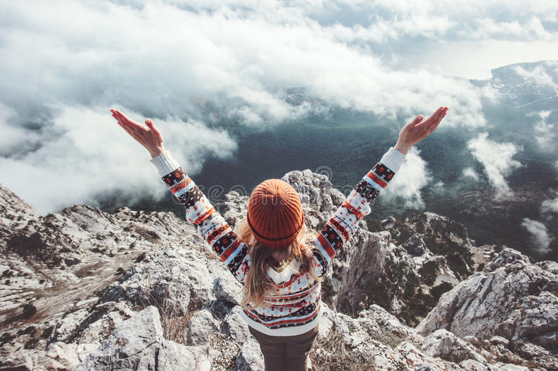 Happy woman traveler on mountain summit hands raised up. Travel Lifestyle success concept adventure active vacations outdoor over clouds harmony with nature stock image